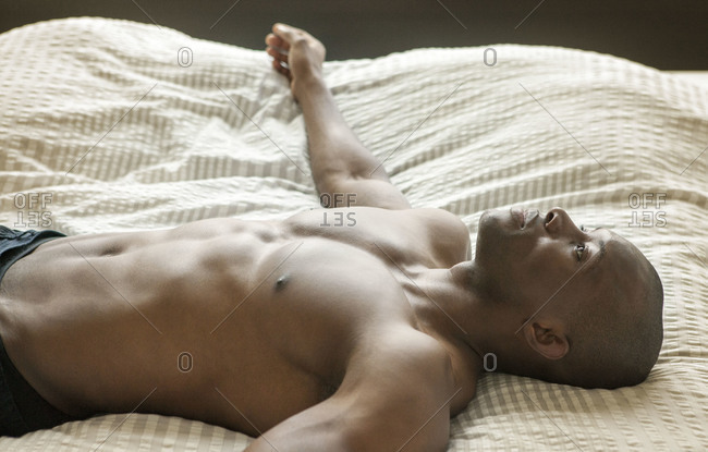 Shirtless African American man spread out in bed