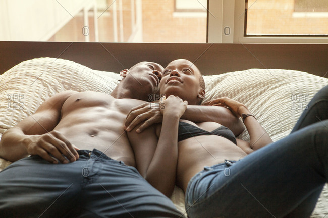African American couple snuggling in bed