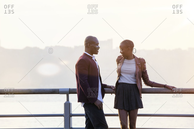 African American couple leaning against rail