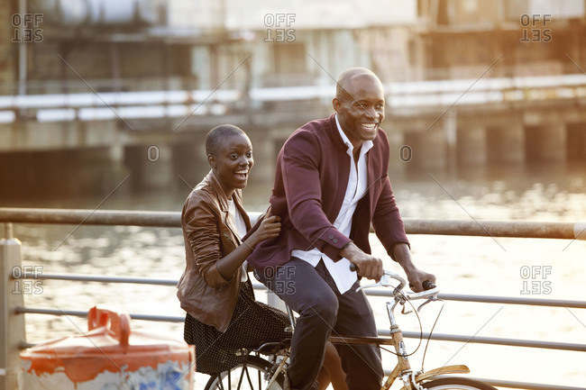 African American couple cycling on pier
