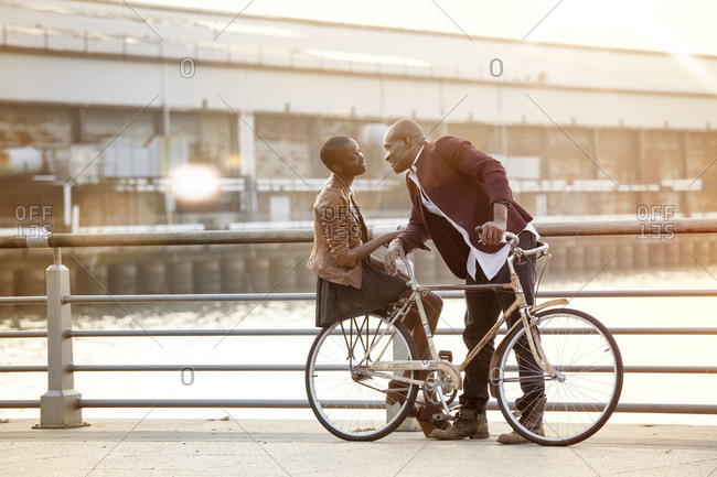 Boyfriend leaning in to kiss girlfriend on bicycle