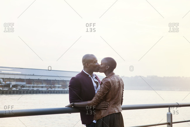 African American couple kissing on pier