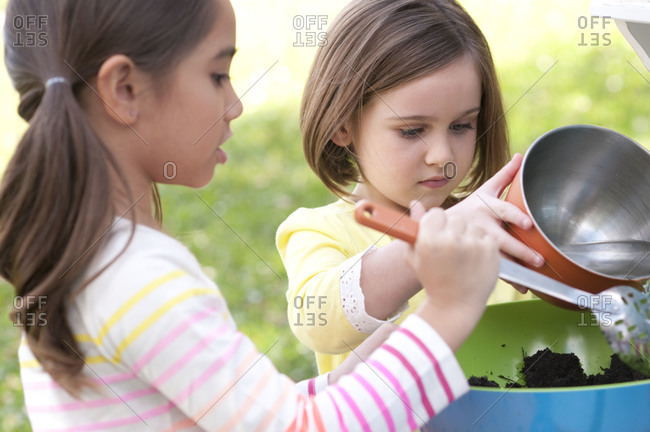 Girls pouring water into a bowl of dirt