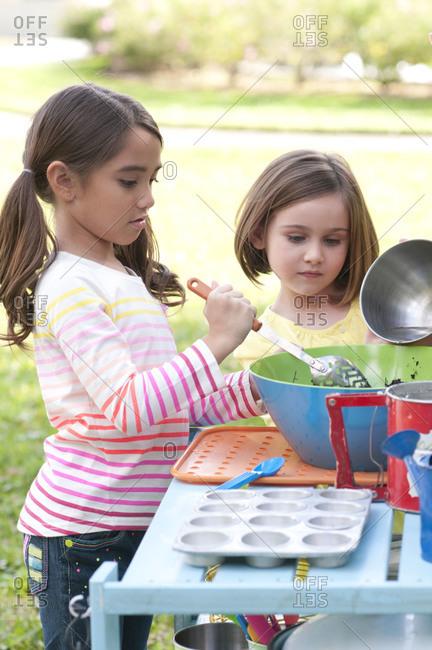 Girls making mud pies in outdoor toy kitchen