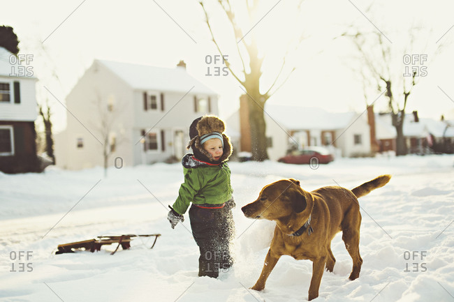 Young boy playing the snow with dog