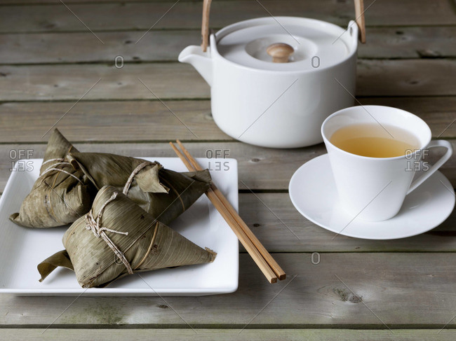 A cup of tea and zongzi wrapped in banana leaves