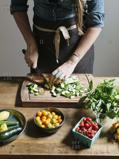 Close-up of a woman slicing up vegetables