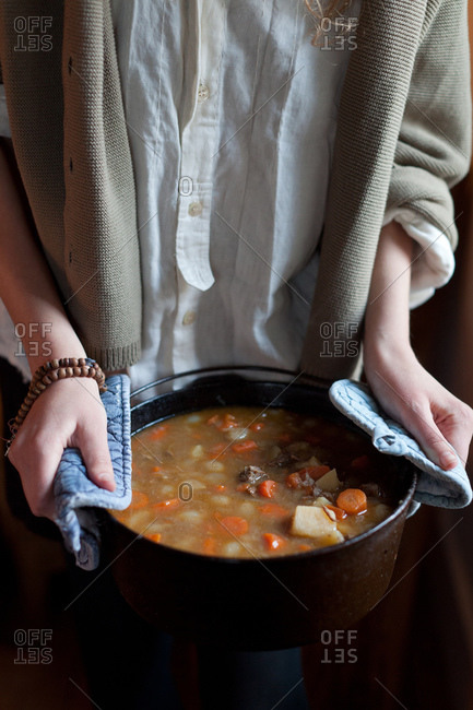 Woman holding warm beef soup in pot