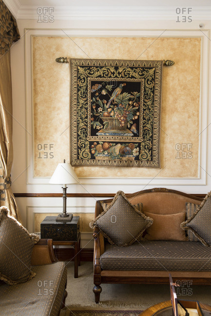 Detail of antique living room with tapestry on wall