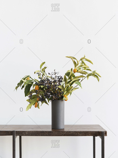 Bouquet of berry flowers in vase on table