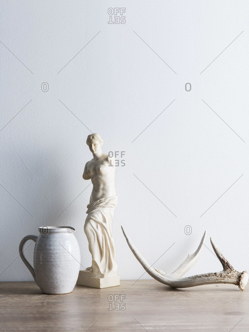 Still life of the statue Venus de Milo and antler on table