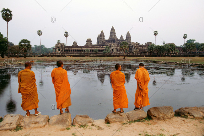 Rear view of four monks standing in front of Angkor Wat