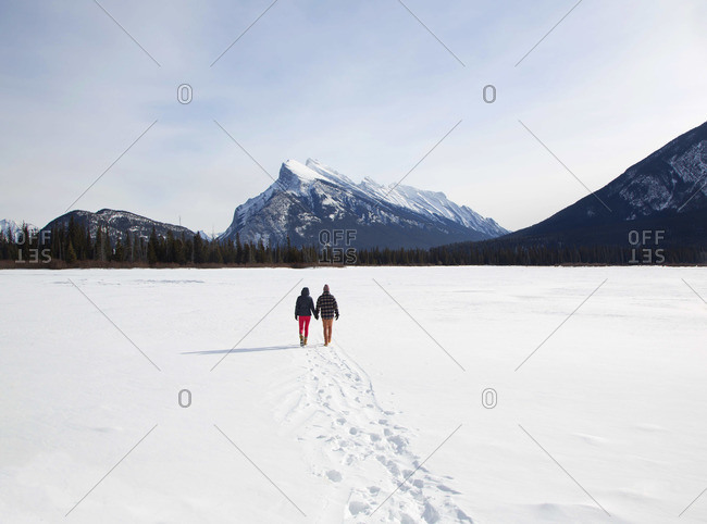 Couple walking hand in hand on a snow field with Mount Rundle in the background