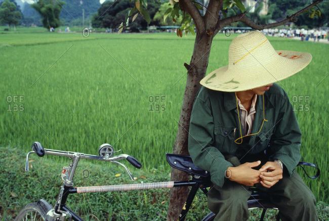 Rice farmer resting on a bike in Guangxi, China