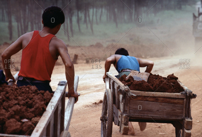 Rear view of laborers moving earth in wooden carts