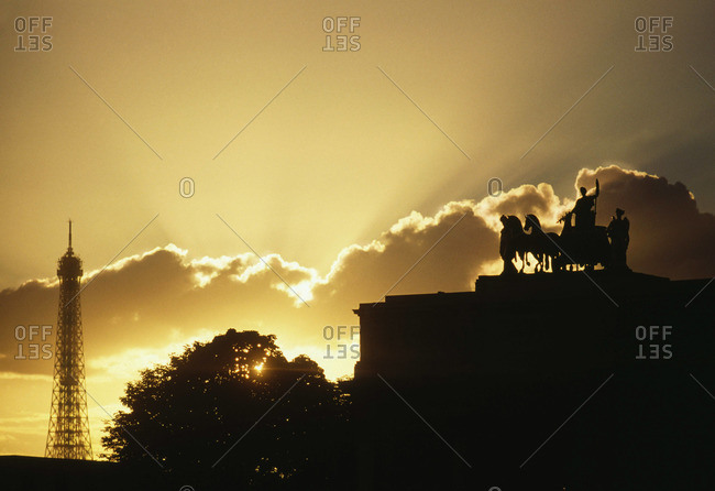 Sunset over Paris with the silhouette of Eiffel Tower and statue atop the Triumphal Arch of Carrousel in France