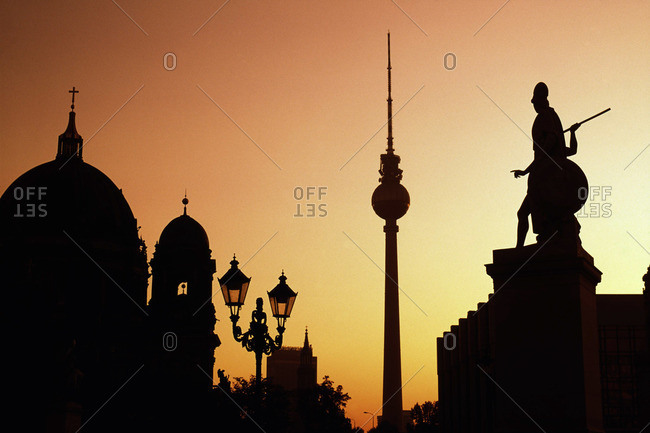Silhouette of the dome of Berlin Cathedral, Berlin TV Tower and statues in Berlin, Germany