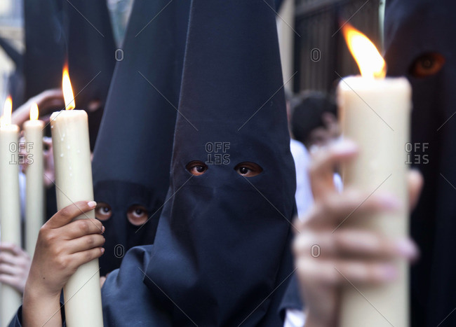 Nazarenos wearing capirote and holding candles during Holy Week of Easter in Seville, Spain
