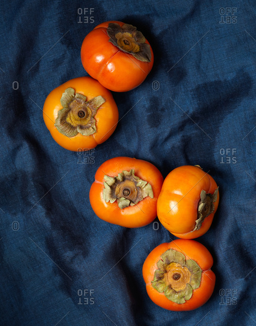 Top view of ripe persimmons on dark blue background
