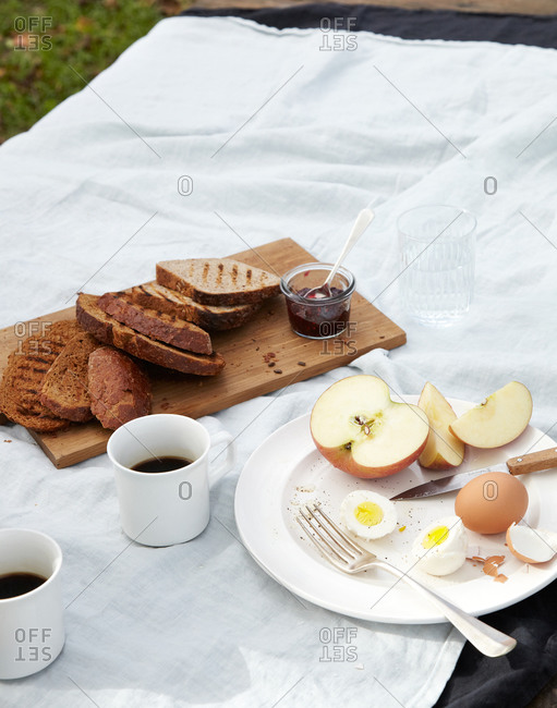 Sliced apple, boiled egg and toast on a table