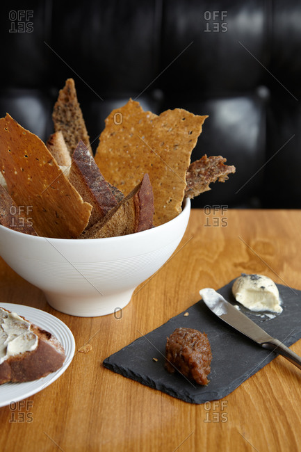Various kind on breads in a bowl and a cheese plate