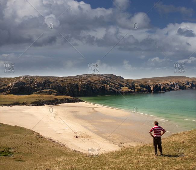Man standing at the beach on the west coast of the island of Lewis near Valtos, Scotland