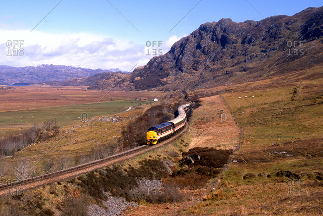 Train passing through a valley in Scotland