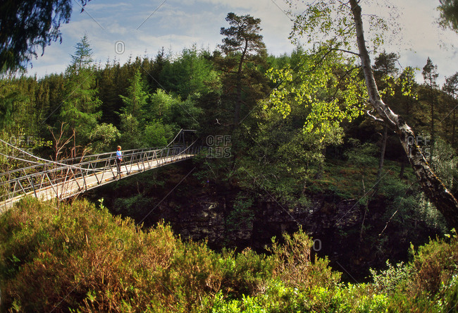 Woman standing on a footbridge at Corrieshalloch gorge