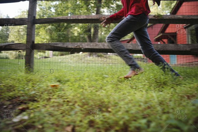 Lower section of girl running by fence