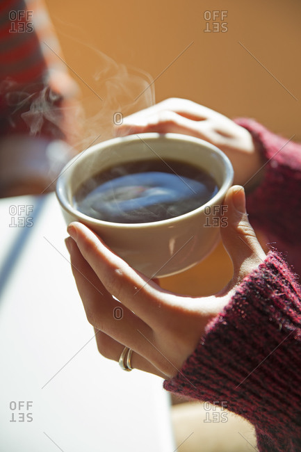 Woman holding a cup of hot coffee in her hands