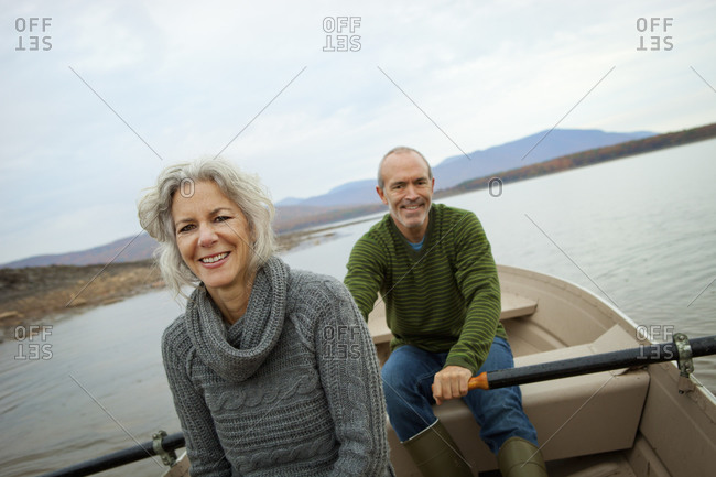Older couple sitting in a rowing boat on the water on an autumn day.