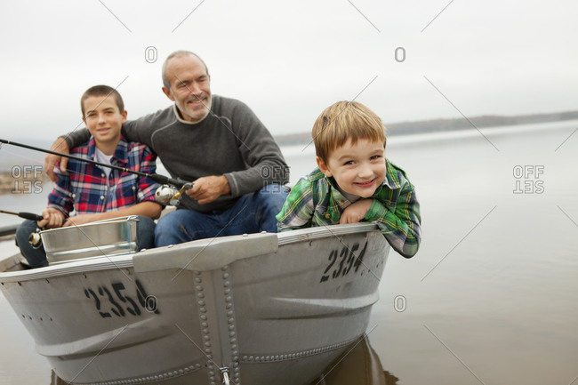 Man and two boys fishing from a boat.