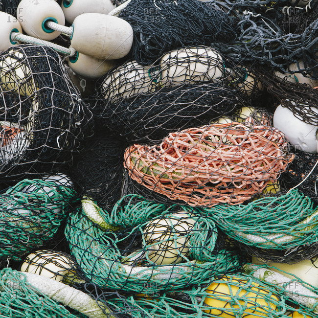 Pile of commercial fishing nets with white floats.