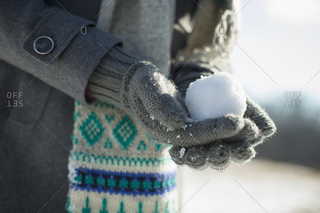Young woman holding a small snowball in her gloved hands.