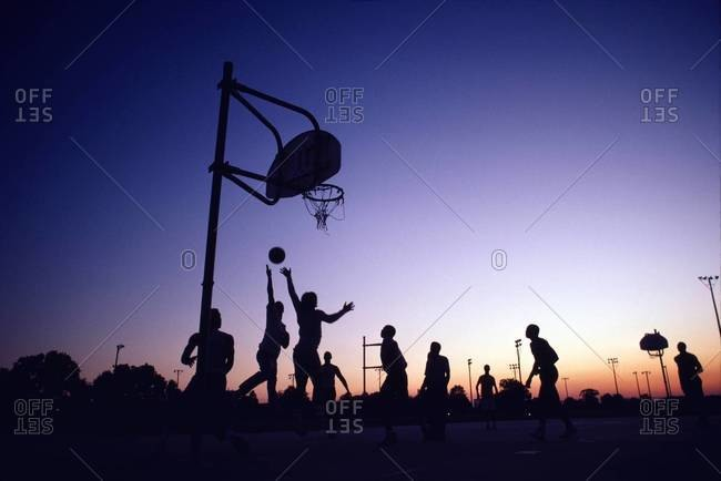 Group of young men playing street basketball, Louisiana