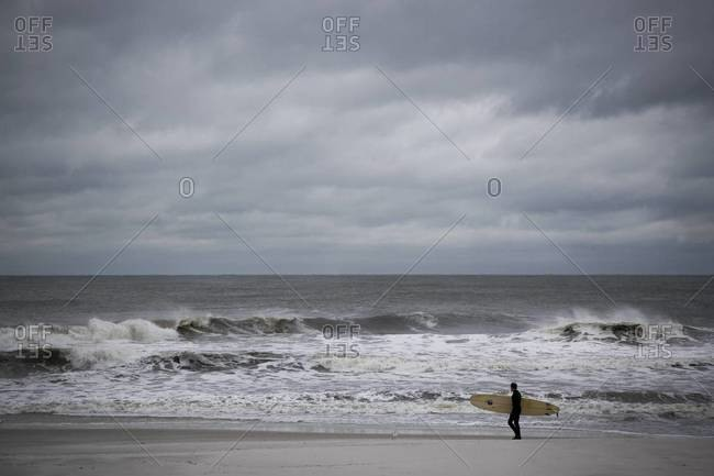 Surfer carrying his surfboard down the beach