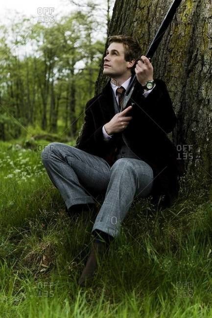Elegant hunter with shotgun sitting beneath the tree