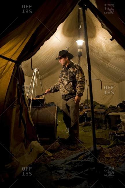 Hunter cooking dinner in tent