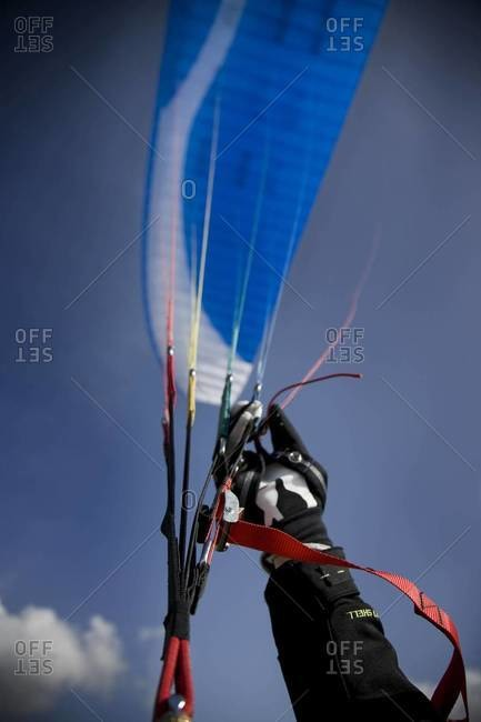 Detail of paraglide's hand with glide above