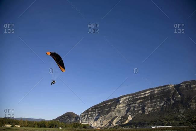 Soaring paraglider against blue sky