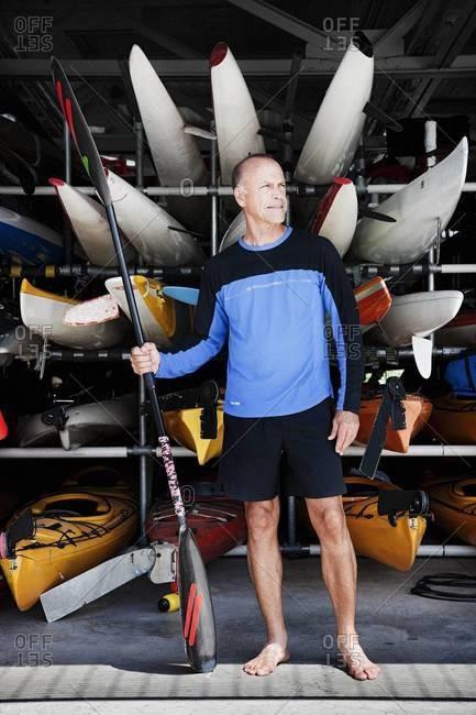 Kayaker standing on pier with an oar