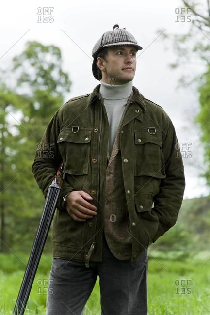 Portrait of elegant hunter with shotgun