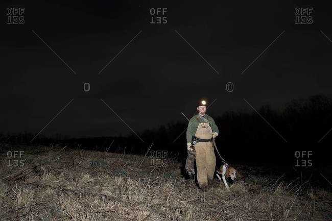 """Hunter with """"coon dog"""" walking in field"""