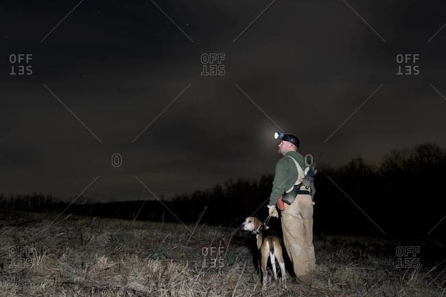 "Hunter with ""coon dog"" walking in field"