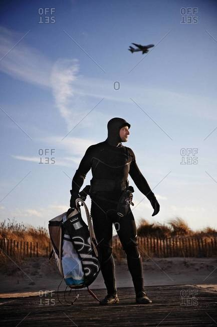 Kiteboarder in wetsuit carrying his package