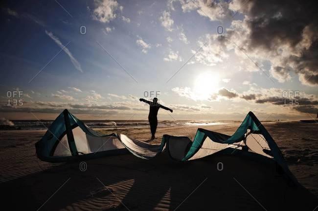 Kiteboarder preparing his kite on the beach