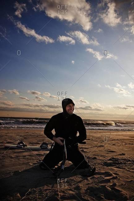 Kiteboarder preparing his harness for kitesurfing on the beach