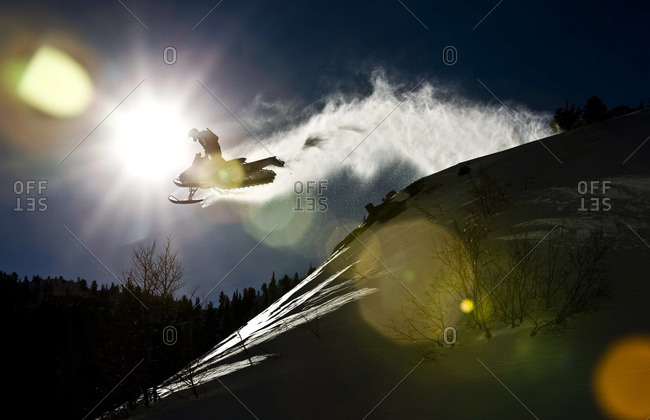 Snowmobile rider jumping in mountains
