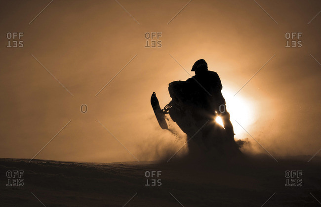 Man riding snowmobile against sunset sky