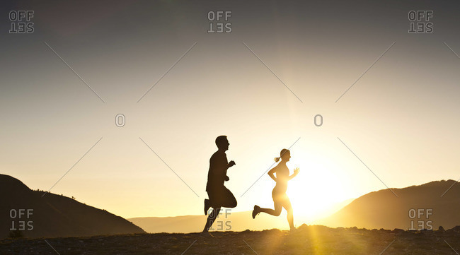 Silhouette of two persons running in dusk